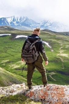 Ein tourist auf einem berggipfel mit rucksack blickt auf eine schöne aussicht auf die berge