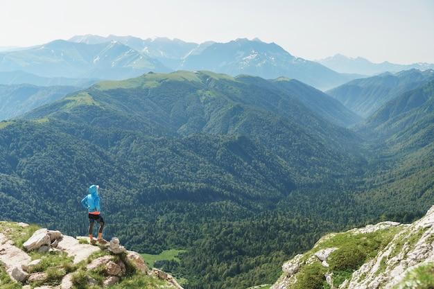 Ein tourist auf einem felsen blickt zurück und blickt in das tal der schlucht und die berge.