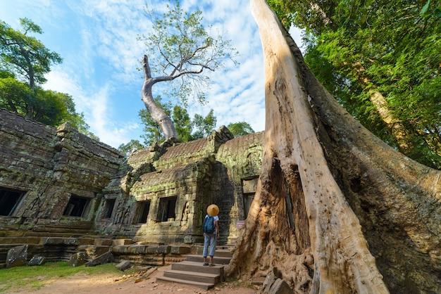Ein tourist, der angkor-ruinen unter dschungel, angkor wat tempelkomplex, reiseziel kambodscha besucht. frau mit traditionellem hut, hintere ansicht.