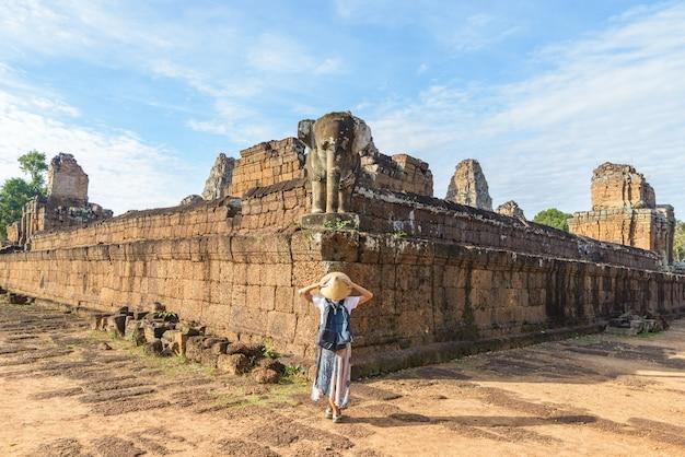 Ein tourist, der angkor wat ruinen am sonnenaufgang besucht