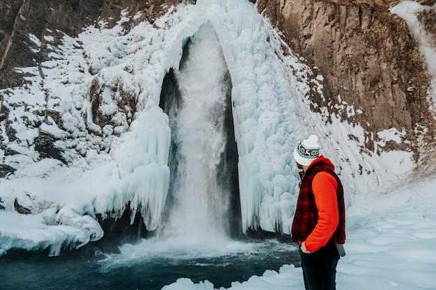 Ein tourist mit dem rücken schaut in die ferne zum winterwasserfall.