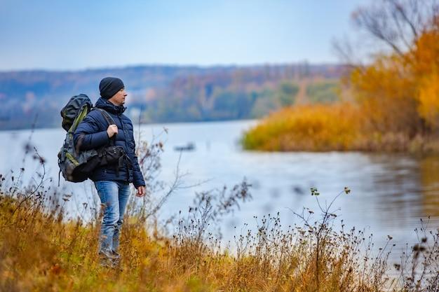 Ein tourist mit einem rucksack betrachtet das andere ufer des flusses im herbst.