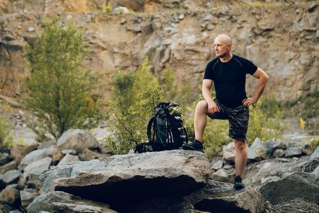 Ein tourist mit einem rucksack steht auf einem felsen und wirft für ein foto auf. der reisende ist beeindruckt von der landschaft um ihn herum