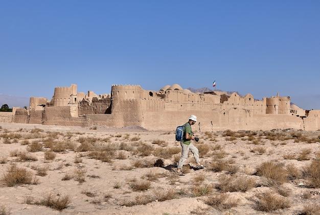 Ein tourist mit kamera geht an der wand der alten persischen festung saryazd entlang.