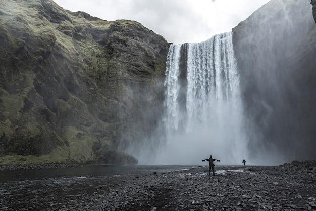 Ein tourist mit offenen armen am grund des skogafoss-wasserfalls im goldenen kreis im süden islands