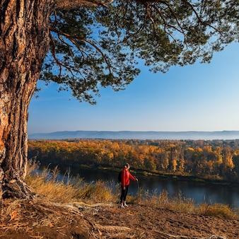 Ein tourist mit rucksack steht auf einem hügel und schaut auf den fluss, den wald und die wunderschöne herbstlandschaft.