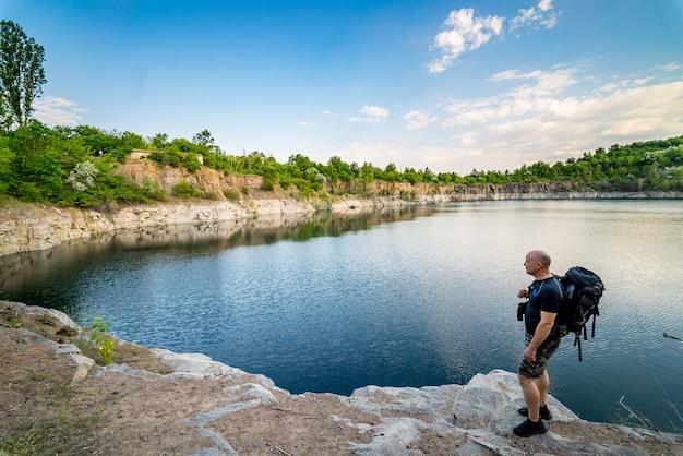 Ein tourist mit rucksack steht in der nähe des steinbruchs.