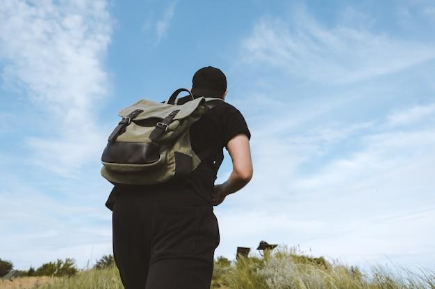 Ein tourist mit rucksack steigt auf einen berg