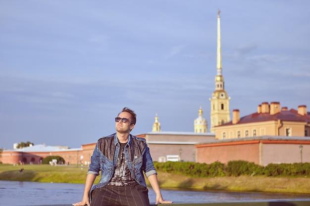Ein tourist mit sonnenbrille verbringt seinen urlaub in der nähe des flusses im zentrum von sankt petersburg, russland.