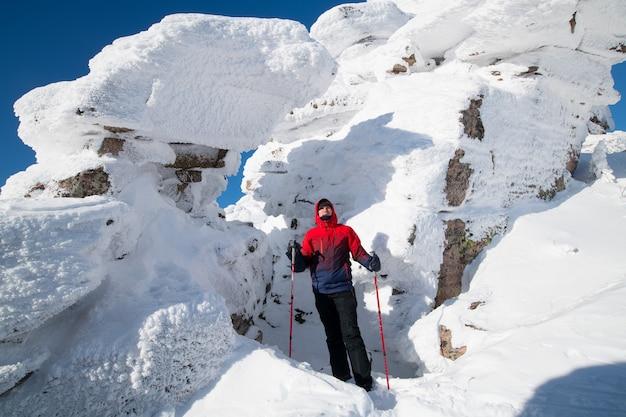 Ein tourist steht auf einem berg in einem schneebedeckten polaren winter bei sonnigem wetter