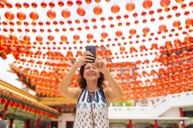Ein touristenmädchen fotografiert die festlichen neujahrsdekorationen mit chinesischen laternen des chinesischen tempels