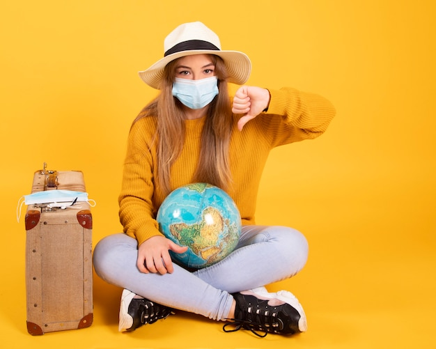 Ein touristenmädchen mit einer medizinischen maske, ausbruch des coronavirus covid-19. konzept der stornierten reisen. ein tourist kann wegen einer pandemie nicht abreisen.