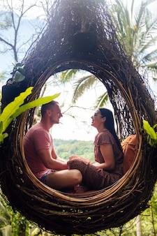 Ein touristenpaar, das auf einem großen vogelnest auf einem baum auf bali insel sitzt