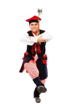 Ein traditioneller polnischer tänzer, der auf weißem hintergrund tanzt