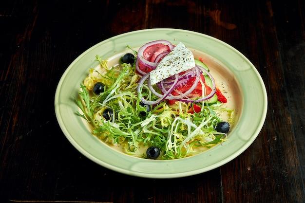 Ein traditionelles griechisches gericht - griechischer salat mit roten zwiebeln, oliven, tomaten und feta, serviert auf einem teller