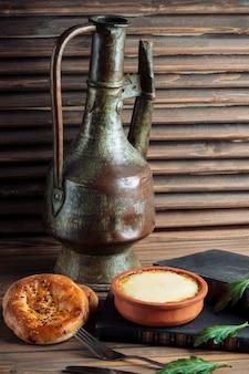 Ein traditionelles tandirbrötchen mit einem topf joghurt.