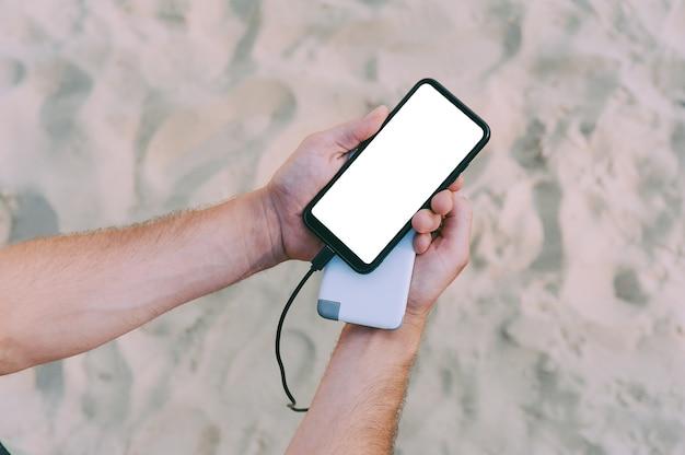 Ein tragbares ladegerät in den händen eines mannes auf dem platz des strandsandes. powerbank lädt das telefon auf.