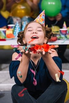 Ein tragender Partyhut des Geburtstagsmädchens auf Kopf, der an Hand fallende Konfetti hält