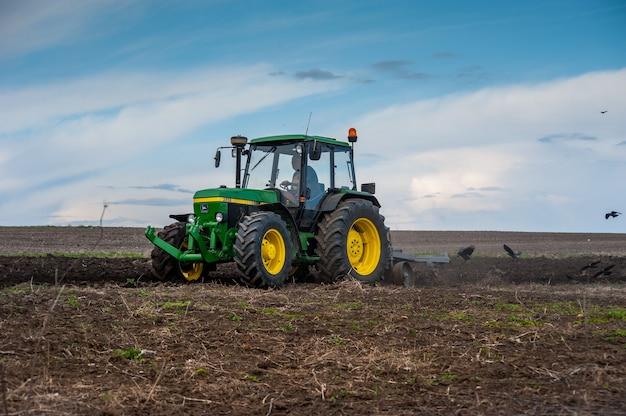 Ein traktor der 90er jahre john deere 2850 mit einem hausgemachten pflug bereitet das feld für die aussaat vor