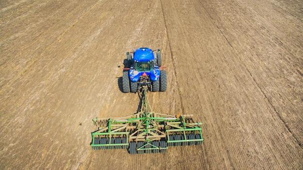 Ein traktor, der auf dem gebiet pflügt und sät