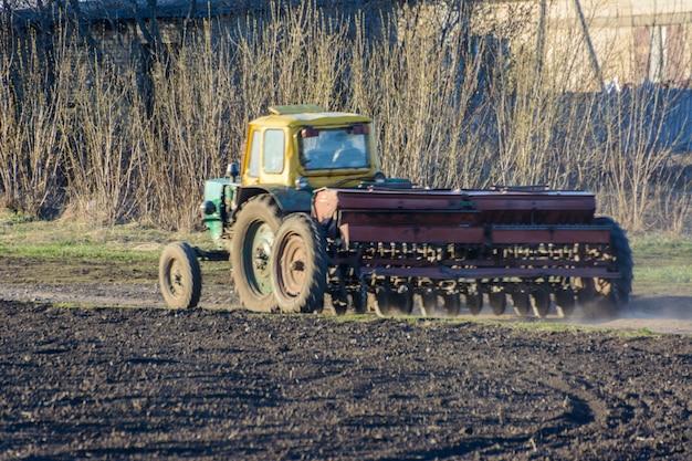 Ein traktor mit grubber kehrt mit einer aussaat auf einer landstraße zurück. der traktor hat die straße komplett blockiert. große transporte verlaufen entlang der straße.
