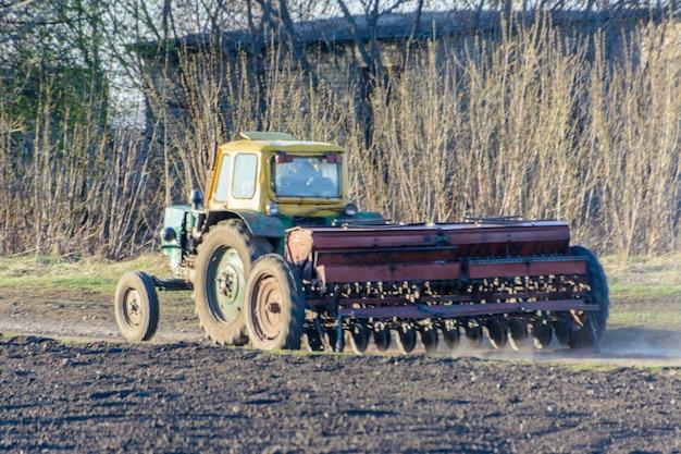Ein traktor mit grubber kehrt mit einer aussaataktion entlang einer landstraße zurück. der traktor hat die straße komplett blockiert. große transporte verlaufen entlang der straße.
