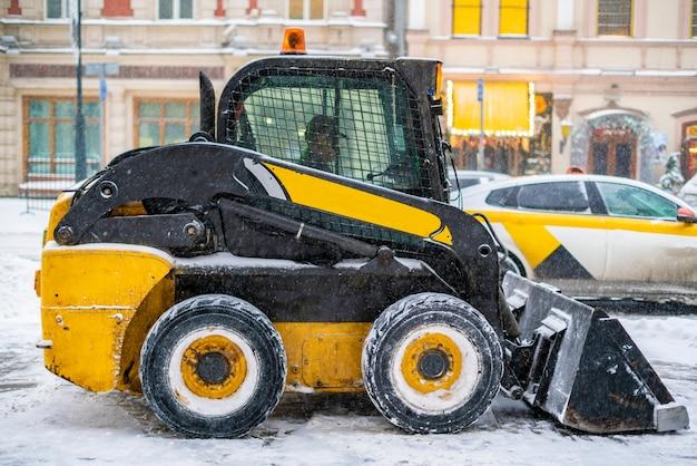 Ein traktor reinigt die straße vom schnee nach einem schneesturm b