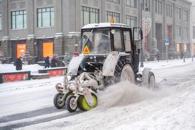 Ein traktor reinigt die straße vom schnee nach einem schneesturm f