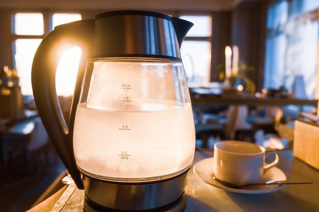 Ein transparenter wasserkessel kocht vor dem hintergrund des sonnenuntergangs, der durch das fenster scheint. das konzept der kaffeepause und des endes des arbeitstages.