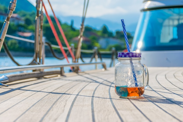 Ein transparentes glas mit einem schönen getränk steht während des restes auf dem deck der yacht.