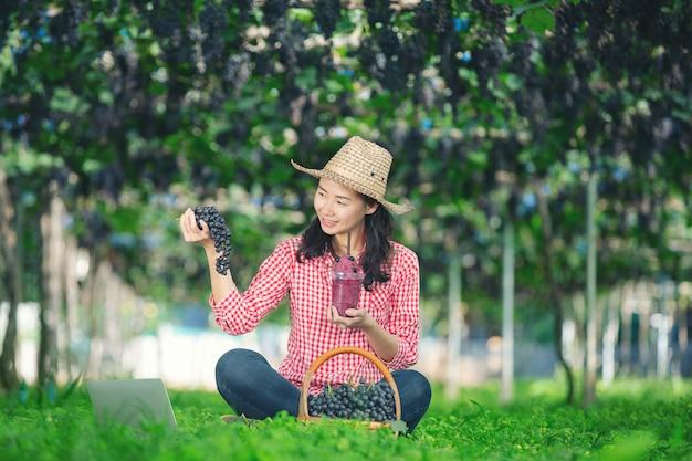 Ein traubenbauer, der frisch gepressten traubensaft genießt