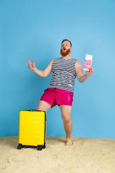 Ein traum wird wahr. glücklicher junger mann mit tasche, die für das reisen auf blauem studiohintergrund vorbereitet wird. konzept der menschlichen gefühle, gesichtsausdruck, sommerferien, wochenende. sommerzeit, meer, meer, alkohol.
