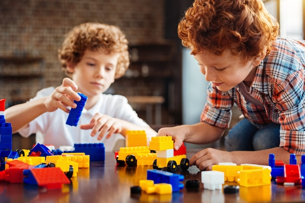 Ein traumauto bauen. selektiver fokus auf ein entzückendes kind, das ein bunt gebautes auto betrachtet, während es auf einem esstisch sitzt und mit seinem älteren bruder zu hause spielt.