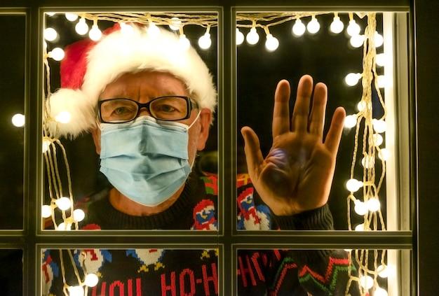 Ein trauriger älterer mann hinter dem beleuchteten fenster in einer weihnachtsmütze trägt aufgrund des coronavirus eine medizinische maske. selbstisolation, um eine ansteckung zu vermeiden