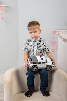 Ein trauriger junge sitzt auf einer stuhllehne und hält ein großes spielzeugauto in den händen. kindheitskonzept.