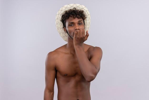 Ein trauriger junger gutaussehender dunkelhäutiger mann mit lockigem haar, der sonnenhut trägt, hält hand auf gesicht, während