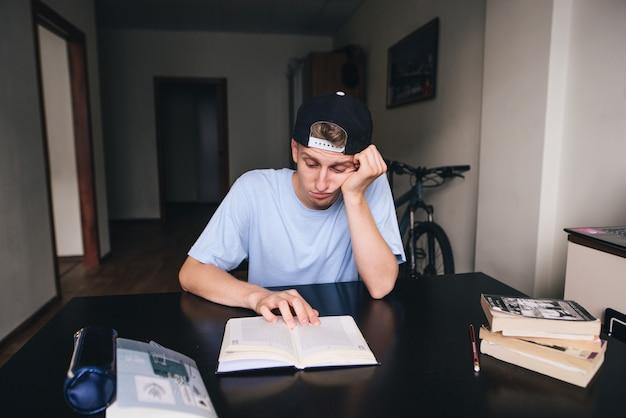 Ein trauriger student liest nur ungern ein buch in seinem zimmer. hausaufgaben machen. zu hause unterrichten