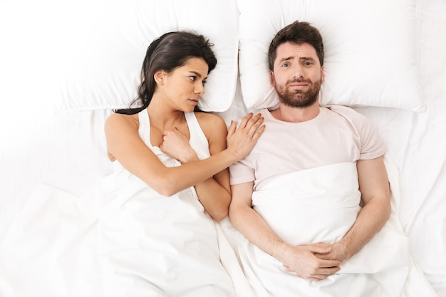 Ein trauriges liebespaar liegt im bett unter einer decke und redet miteinander