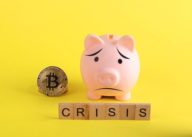 Ein trauriges sparschwein mit bitcoins und titelkrise auf gelbem hintergrund