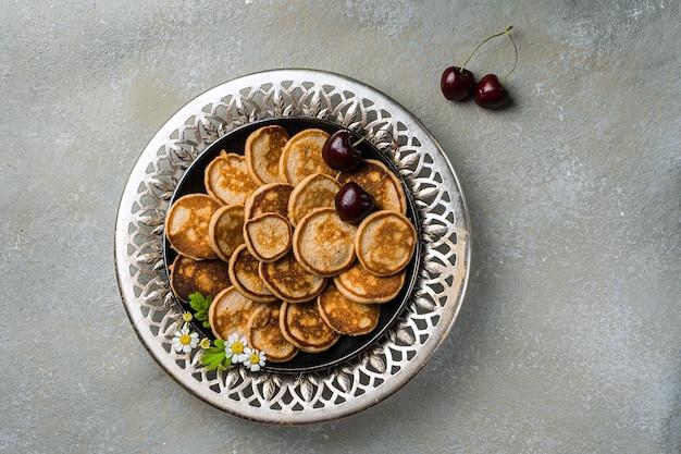Ein trendiges hausgemachtes frühstück mit kleinen pfannkuchen aus der nähe. mini-pfannkuchen, kirschen, tee auf dem tisch in einem durchbrochenen teller. horizontale ausrichtung