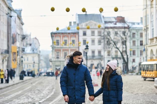 Ein trendiges junges paar geht in der wintersaison durch die stadt.