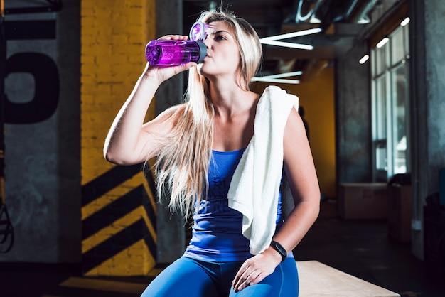 Ein trinkwasser der athletischen frau in der turnhalle