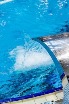 Ein türkisfarbener wasserfall, rücken- und schultermassage im pool.