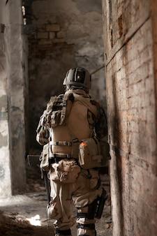 Ein typ in einer amerikanischen militäruniform in einem alten verlassenen gang bewegt sich mit einem airsoft-sportspiel