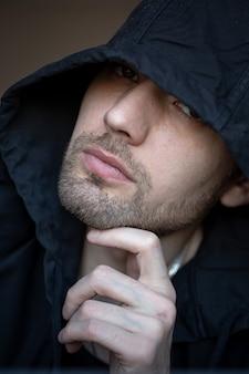 Ein typ in einer schwarzen kapuze mit einem nahaufnahmeportrait.