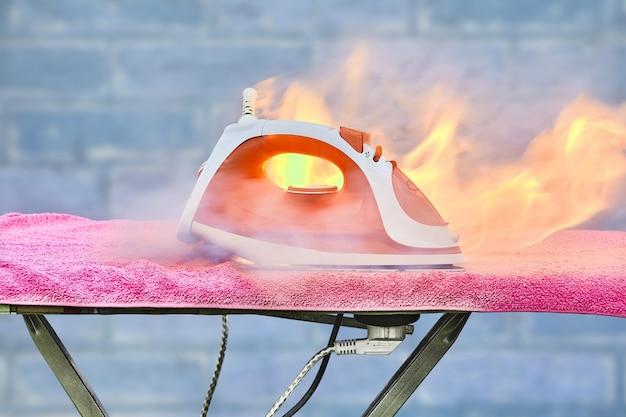 Ein überhitztes haushaltsgerät ist verbrannt vergessenes bügeleisen hat auf dem bügelbrett feuer gefangen