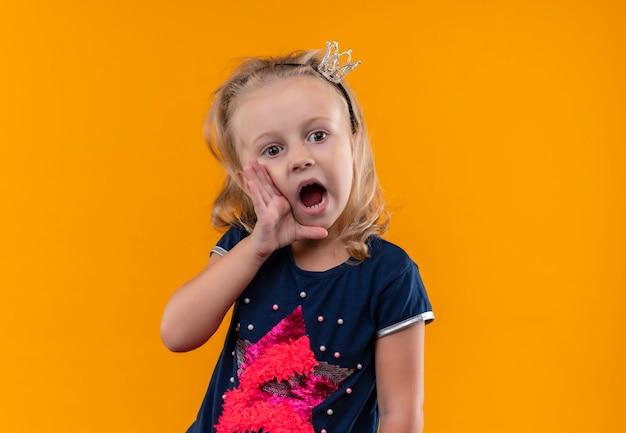 Ein überraschend hübsches kleines mädchen, das ein dunkelblaues hemd im kronenstirnband trägt und jemanden mit den händen auf ihrem mund an einer orangefarbenen wand anruft