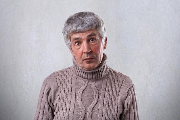 Ein überraschter alter mann mit dunklen augen, der falten im gesicht und grauem haar trägt und einen braunen pullover trägt, der direkt schaut