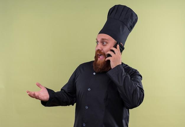 Ein überraschter bärtiger kochmann in der schwarzen uniform, die auf handy an einer grünen wand spricht