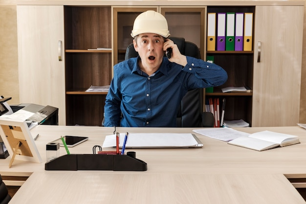 Ein überraschter chef mit bauhelm am tisch in seinem büro schreit etwas ins telefon. wichtige nachrichten. onlinekommunikation. geschäftsmann.